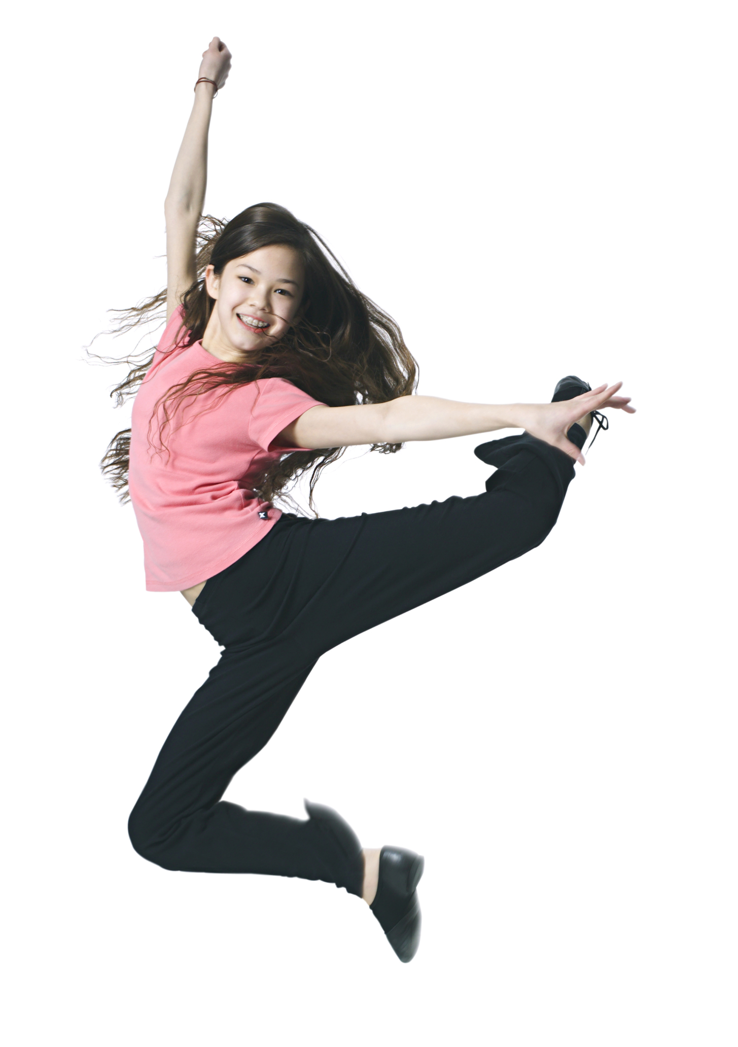 Full Body Shot Of A Female Child As She Playfully Dances And Jumps Through The Air